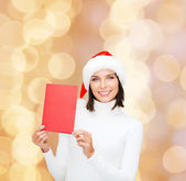 Smiling woman in santa hat with greeting card — Stock Photo