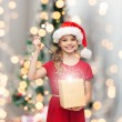Smiling girl in santa helper hat with gift box — Stock Photo #54851215