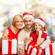 Happy family in santa helper hats with gift boxes — Stock Photo #54851403