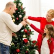 Smiling family decorating christmas tree at home — Stock Photo #54853507