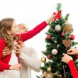 Smiling family decorating christmas tree at home — Stock Photo #54853511