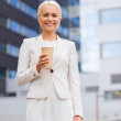 Smiling businesswoman with paper cup outdoors — Stock Photo #54853627
