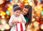 Happy mother and little girl with gift box — Stock Photo