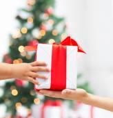 закройте рук ребенка и матери с подарочной коробке — Стоковое фото