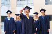 Group of smiling students in mortarboards — Stock Photo