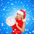 Smiling woman in santa helper hat with clock — Stock Photo #55074891