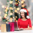 Smiling woman in santa hat with bags and laptop — Stock Photo #55078541