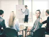 Businesswoman with team showing thumbs up — Stock Photo