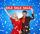 Smiling couple with red sale sign — Stock Photo