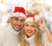 Smiling couple in sweaters and santa helper hats — Stock Photo