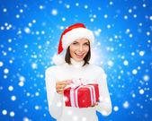 Donna sorridente in santa helper cappello con scatola regalo — Foto Stock