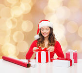 Smiling woman in santa helper hat packing gifts — Stock Photo