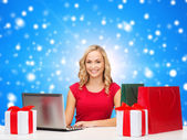 Smiling woman in red shirt with gifts and laptop — Stock Photo