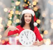 Smiling woman in santa helper hat with clock — Stockfoto