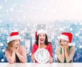 Usmívající se ženy v santa hat pomocníka s hodinami — Stock fotografie