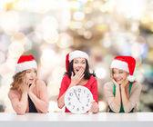 Usmívající se ženy v santa čepice pomocníka s hodinami — Stock fotografie