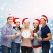 Group of teenagers in santa helper hats with clock — Stock Photo #55080221