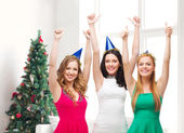 Smiling women in party caps showing thumbs up — Stock Photo