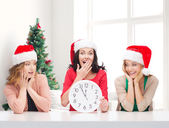 Smiling women in santa helper hats with clock — Stock Photo