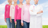Close up of women with cancer awareness ribbons — Stockfoto