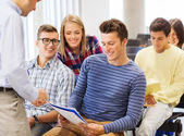 Group of students and teacher with notebook — Stock Photo