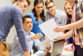 Group of students and teacher with laptop — Stock Photo