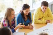 Group of smiling students with blueprint — Stock Photo