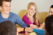 Group of smiling students with hand on top — Stock Photo