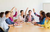 Group of smiling students voting — Stock Photo