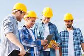 Grupo de construtores sorridentes com tablet pc ao ar livre — Fotografia Stock