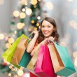 Smiling woman with colorful shopping bags — Stock Photo #55410537