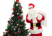Santa claus with bag and christmas tree — Stock fotografie