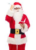 Hombre en traje de santa claus con bloc de notas — Foto de Stock