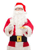 Santa claus with glass of milk and cookies — ストック写真