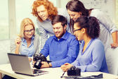 Smiling team with laptop and photocamera in office — Stock Photo