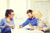 Smiling team with table pc and papers working — Stock Photo