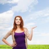 Smiling teenage girl holding something on her palm — Stock Photo