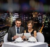 Couple with menus on tablet pc at restaurant — ストック写真