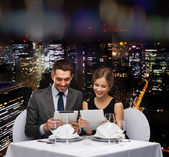 Couple with menus on tablet pc at restaurant — Zdjęcie stockowe