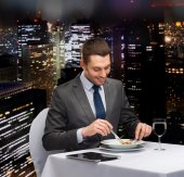 Smiling man with tablet pc eating main course — ストック写真