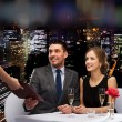 Waiter giving menu to happy couple at restaurant — Stock Photo #55531131