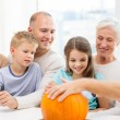 Happy family sitting with pumpkins at home — Stock Photo #55534331