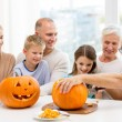 Happy family sitting with pumpkins at home — Stock Photo #55534353