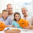 Happy family sitting with pumpkins at home — Stock Photo #55534369
