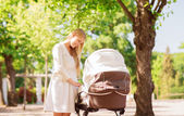 Happy mother with stroller in park — Stockfoto