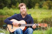 Smiling man playing guitar in camping — Stock Photo