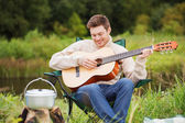 Smiling man with guitar and dixie in camping — Stock Photo
