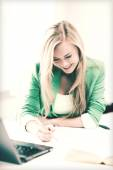 Smiling student girl writing in notebook — Stock Photo