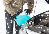Closeup of man pouring antifreeze into car — Stock Photo