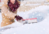 Closeup of woman cleaning snow from car — Stock Photo